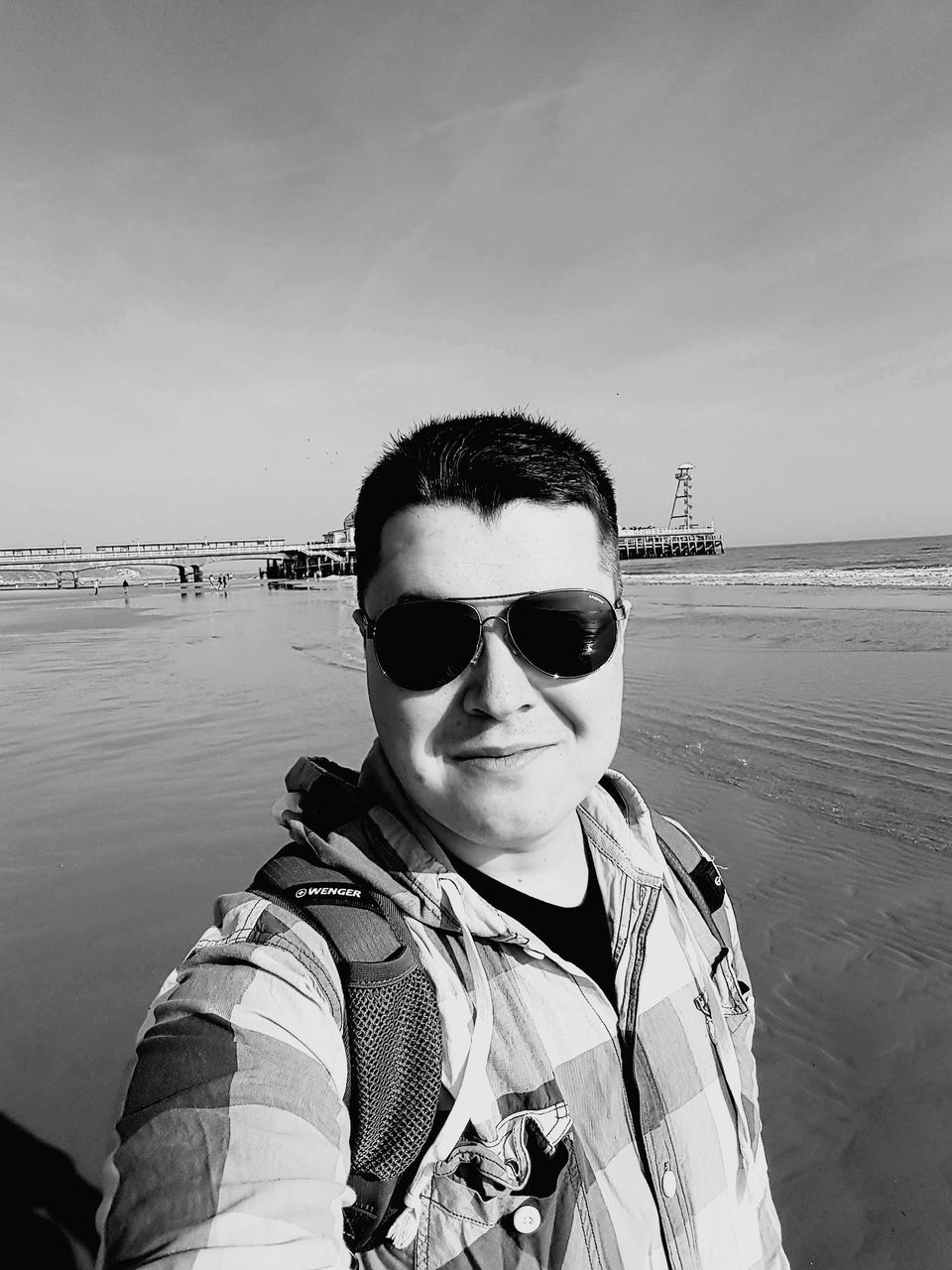 sunglasses, real people, one person, looking at camera, sea, portrait, water, sky, leisure activity, outdoors, standing, day, young adult, beach, lifestyles, nature, horizon over water, clear sky, people