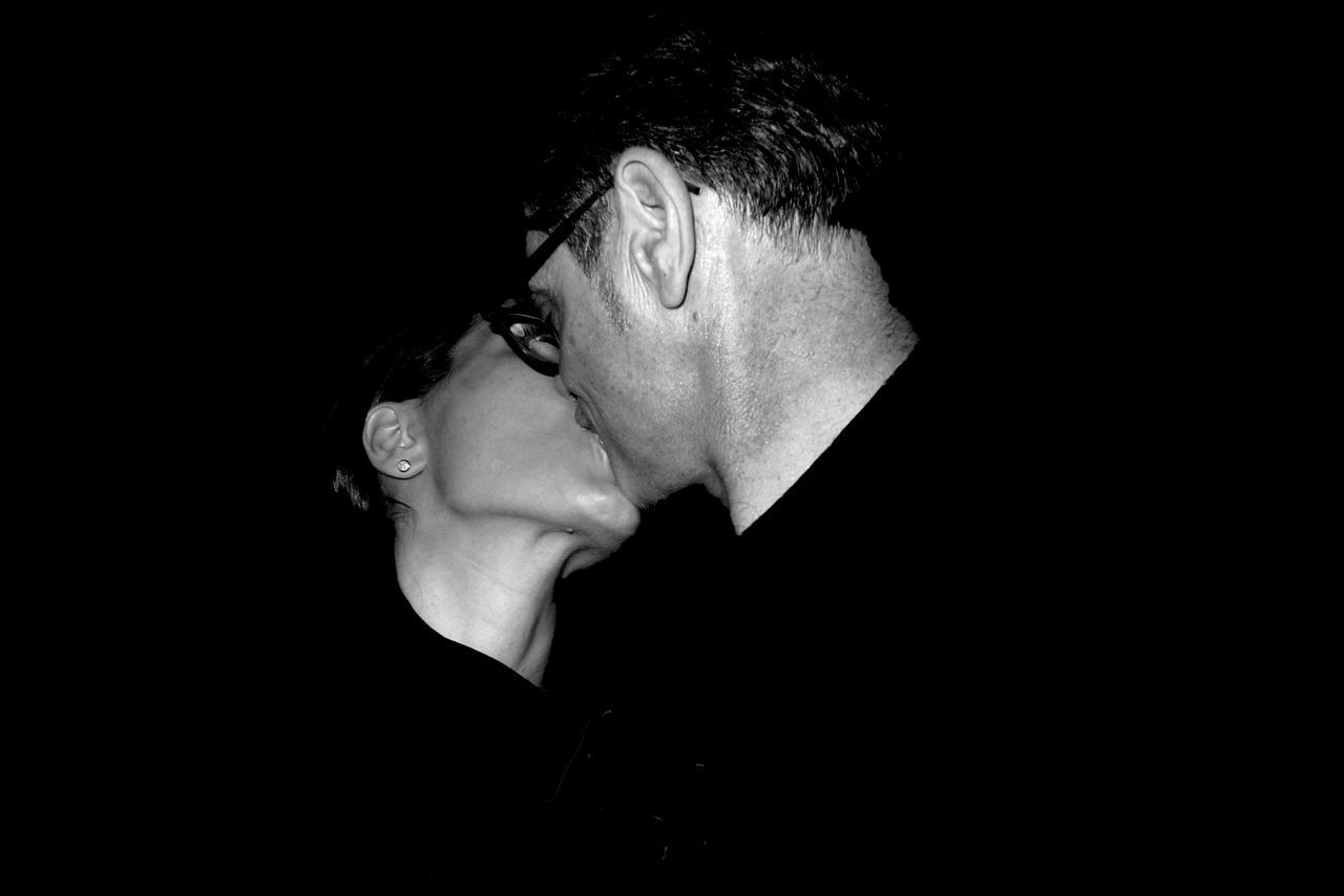 Man And Woman Kissing Against Black Background