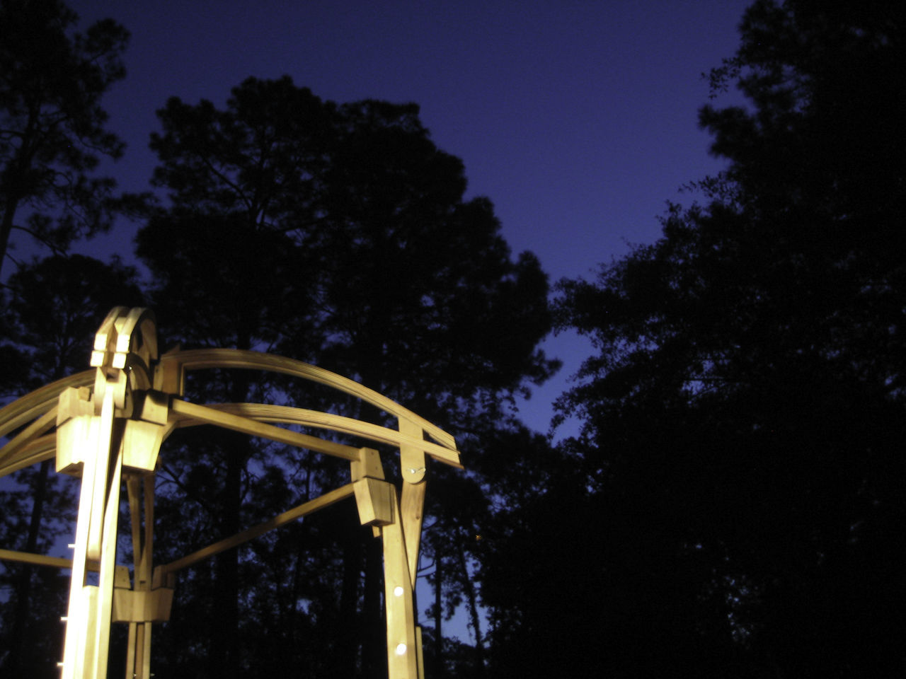 This photograph was taken late at night and focuses on an architecturally designed, hand-built wooden gazebo - which was actually used as a wedding altar. Altar Architectural Detail Architecture Blue Built Structure Dramatic Sky Dusk Gazebo Glow Handmade Low Angle View Moody Sky Night Outdoors Sky Structure Sunset Treescape Woodworking