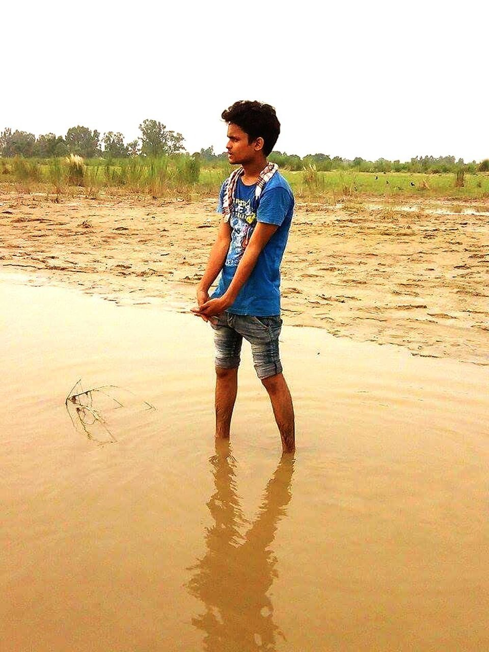 full length, casual clothing, one person, young adult, real people, standing, young women, lifestyles, young men, leisure activity, front view, happiness, water, outdoors, sand, day, nature, smiling, ankle deep in water, tree, sky, people