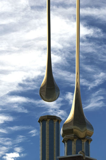 A surreal image of a pair of gold domes on a church. The gold domes are dripping from the sky onto the building and creating the roofs. Architectural Feature Architecture Building Exterior Built Structure City Cloud - Sky Day Dome Drips  Geometric Shape Gold Golden Gooey High Section No People Outdoors Roof Sky Spire  Surrealism Surrealist Art The Architect - 2017 EyeEm Awards