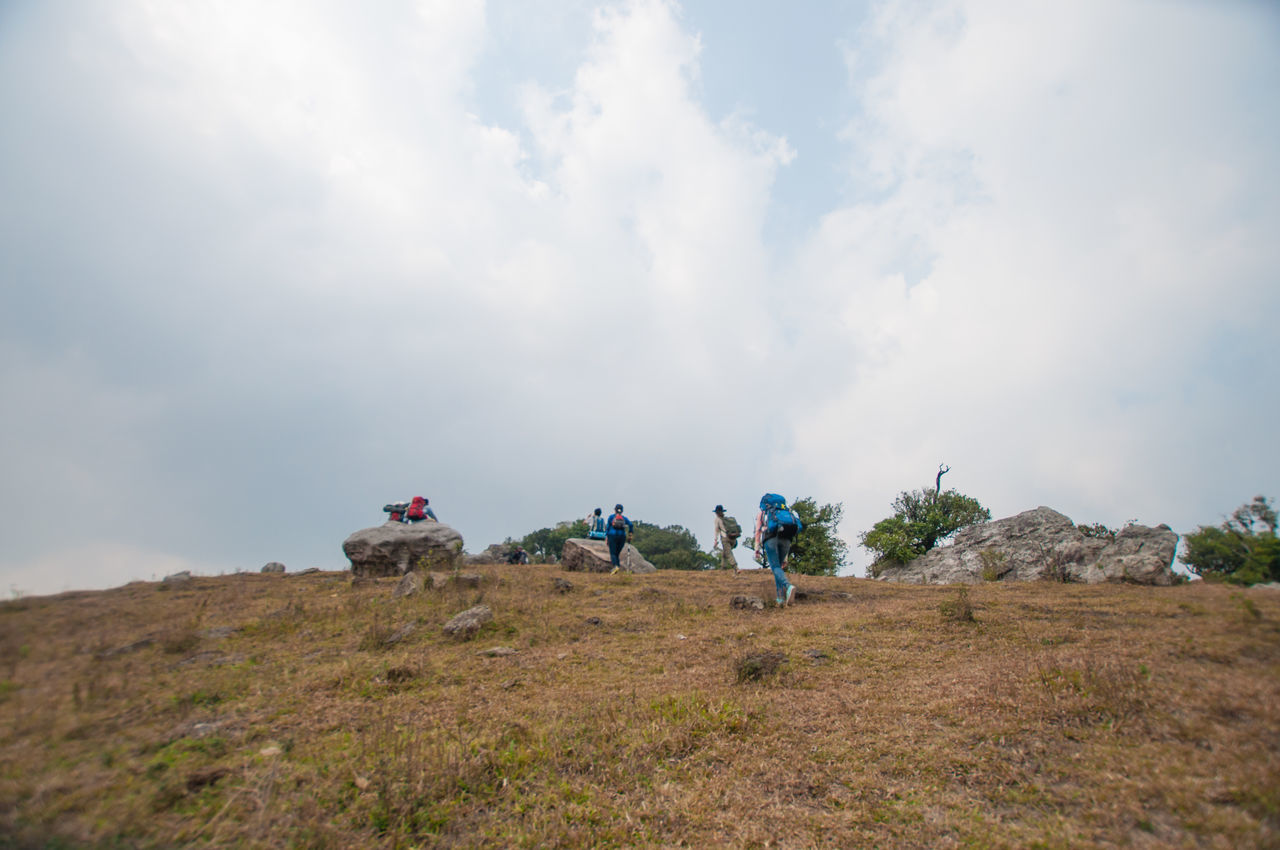Hikers On Hill Against Cloudy Sky