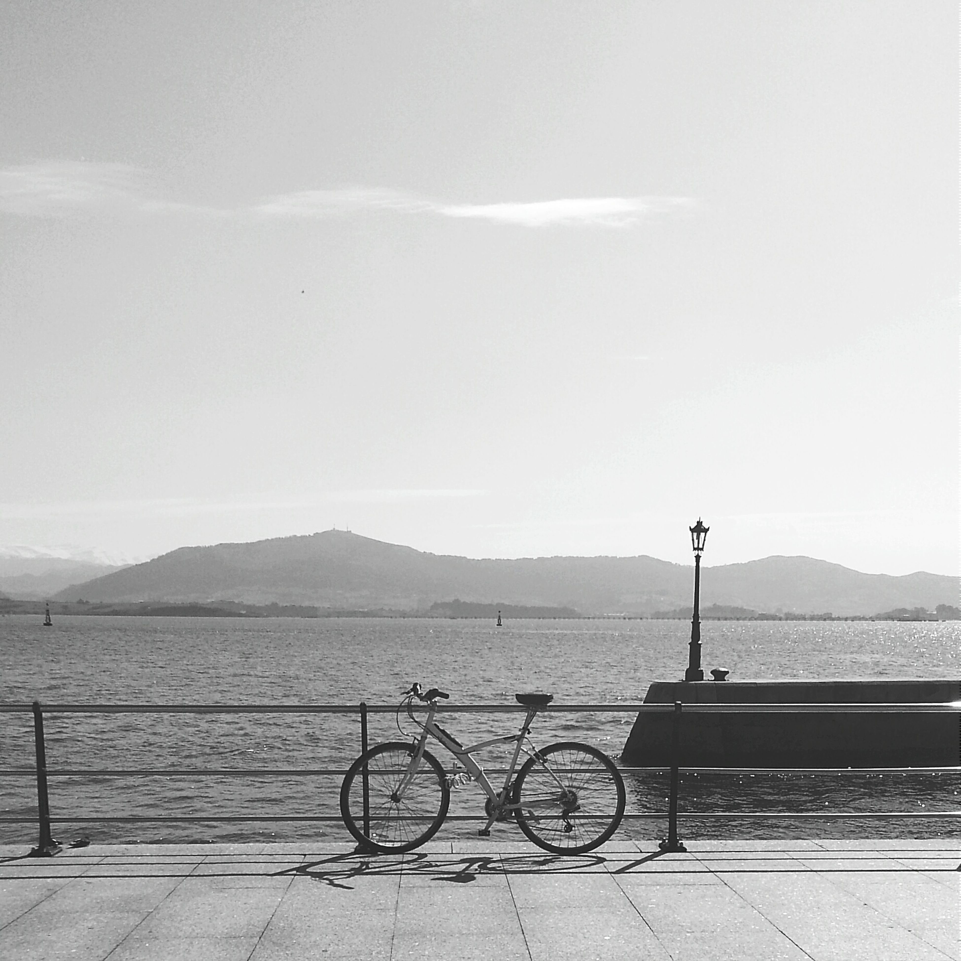 railing, mountain, transportation, sky, sea, water, tranquility, bicycle, tranquil scene, mountain range, scenics, nature, beauty in nature, road, mode of transport, copy space, clear sky, land vehicle, outdoors, day