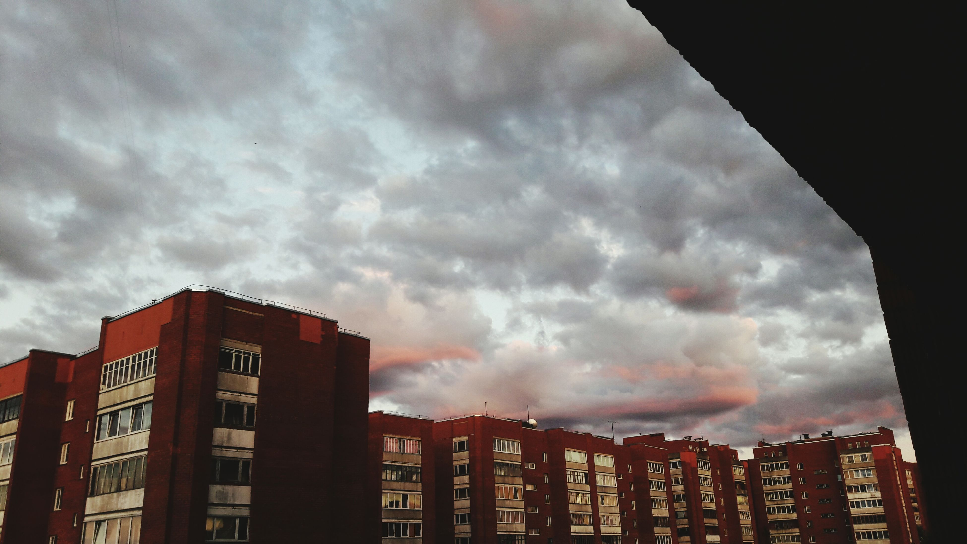 architecture, built structure, building exterior, sky, low angle view, cloud - sky, cloudy, city, building, residential building, weather, residential structure, cloud, overcast, outdoors, no people, high section, dramatic sky, modern, city life, nature