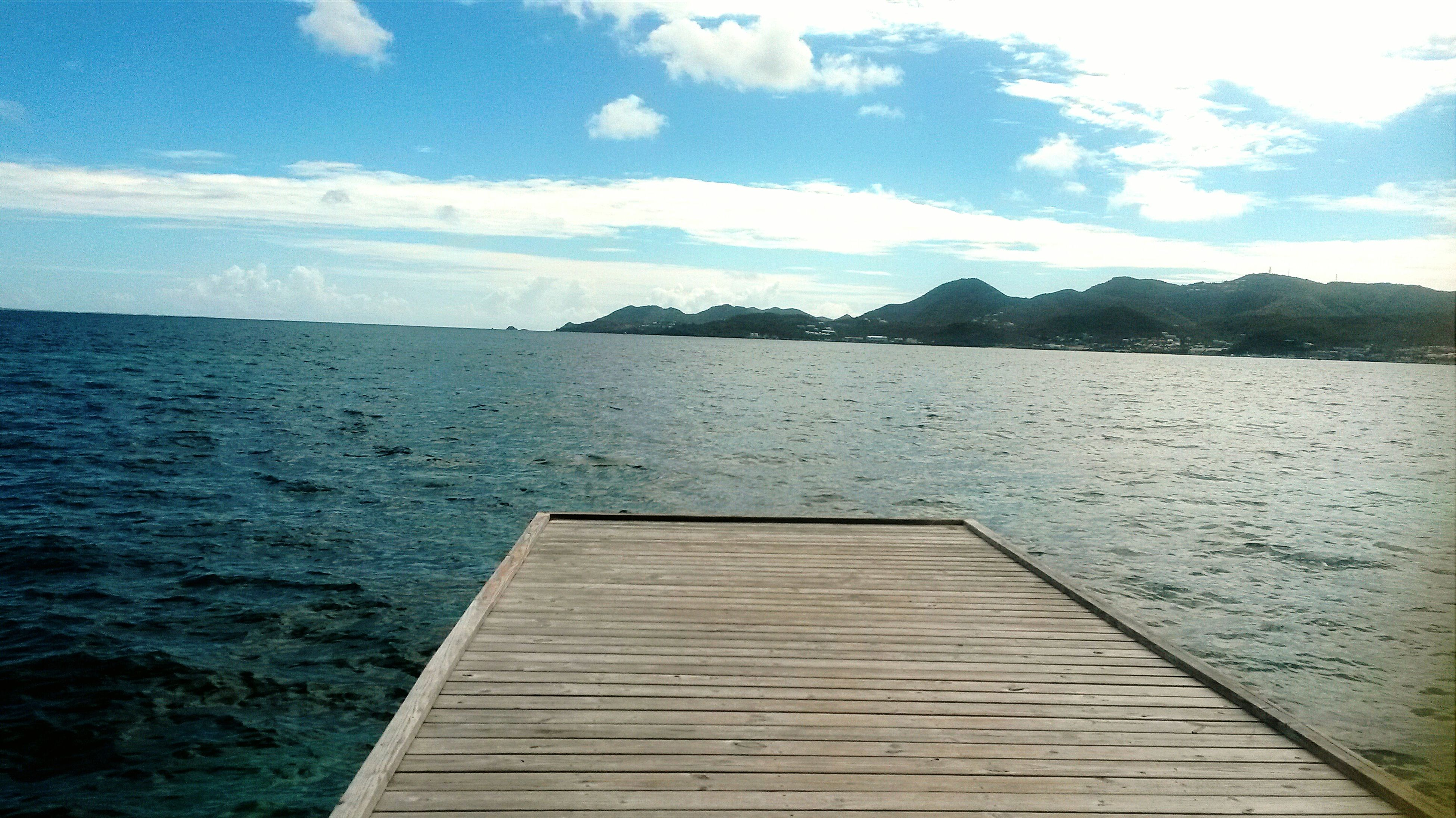 water, tranquil scene, sky, tranquility, scenics, sea, beauty in nature, pier, mountain, nature, blue, lake, idyllic, cloud - sky, rippled, cloud, wood - material, jetty, calm, day