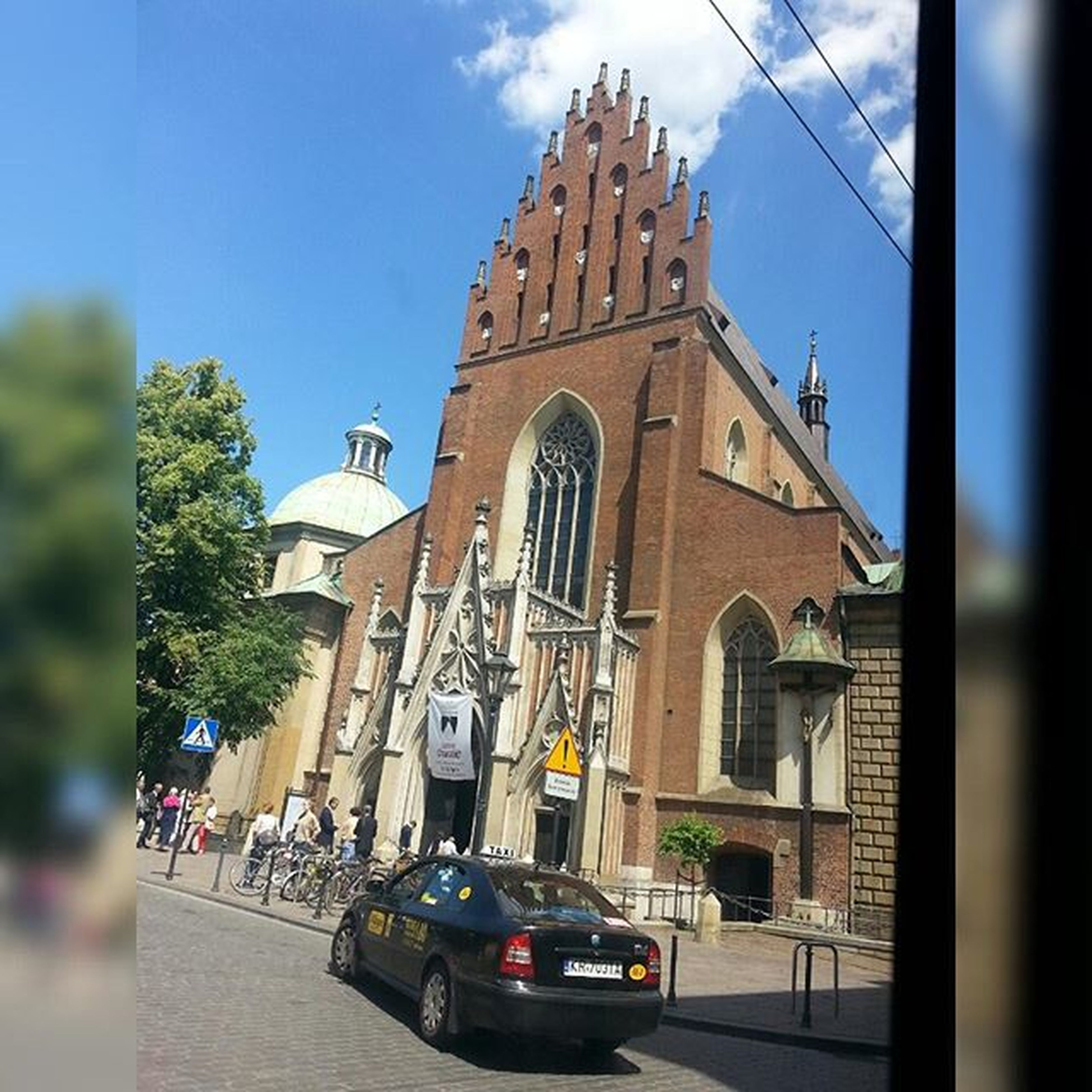 building exterior, architecture, built structure, church, religion, sky, place of worship, spirituality, city, low angle view, window, street, cathedral, car, day, facade, outdoors, transportation