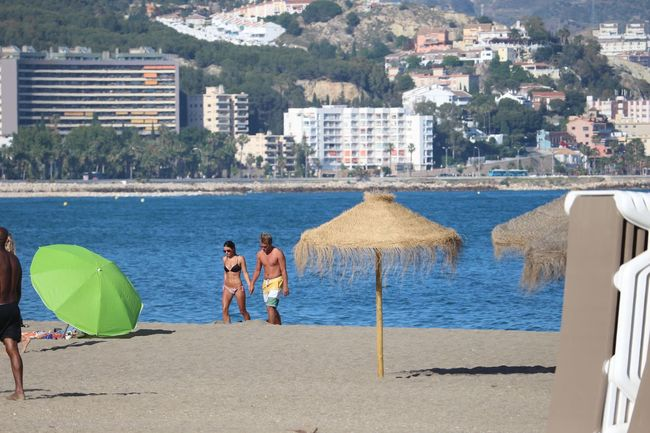 Sea Ocean View Young Couple Beachphotography Sunshine! Hand In Hands Blu Water Straw Umbrella Green Umbrella Cityscape Live Love Shop in Malaga Spain Between the sun umbrellas... Love♥