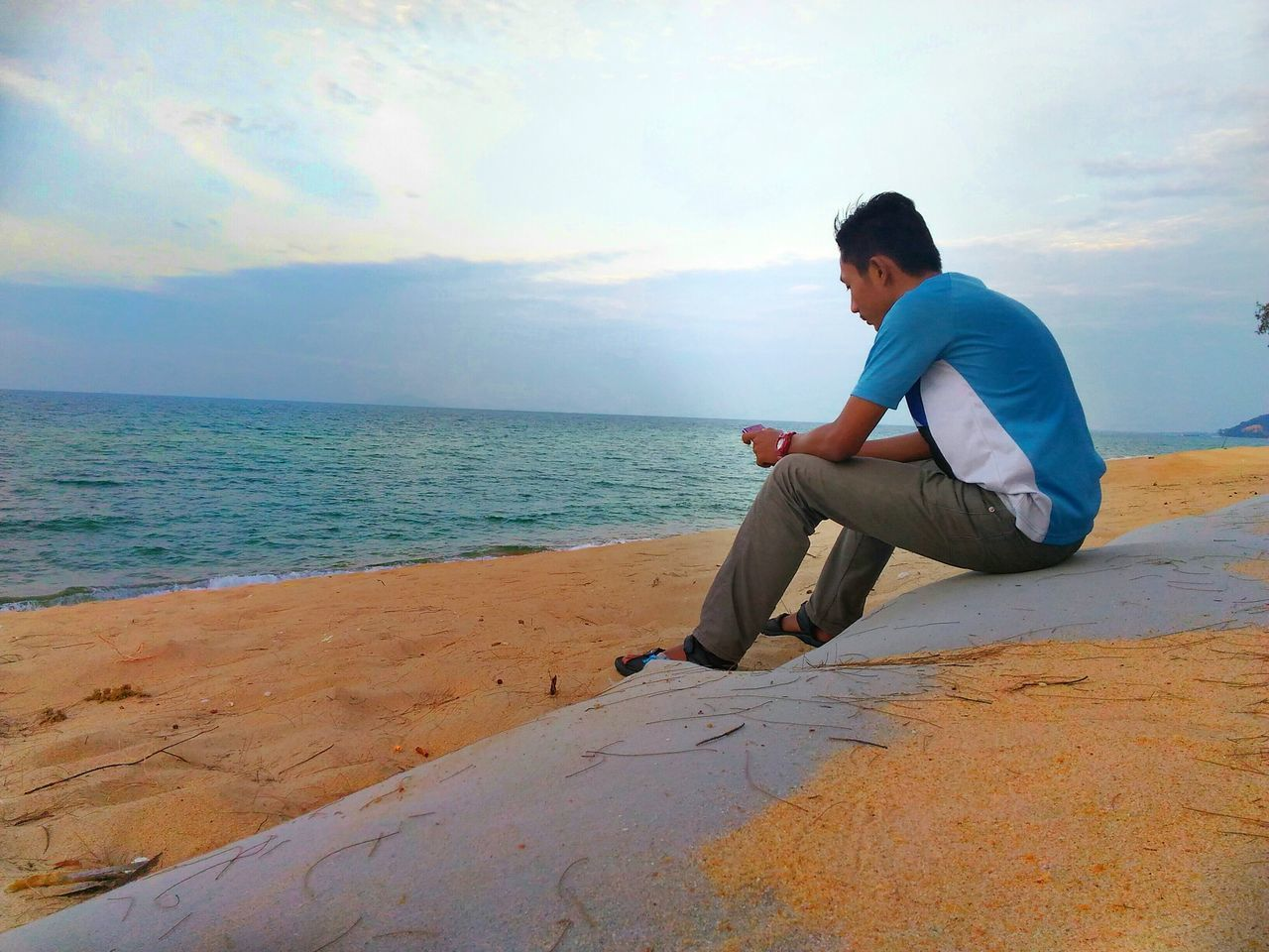 sea, horizon over water, one person, full length, sitting, sky, water, side view, nature, casual clothing, real people, beach, wireless technology, technology, leisure activity, beauty in nature, relaxation, scenics, outdoors, young adult, day, one man only, adult, people