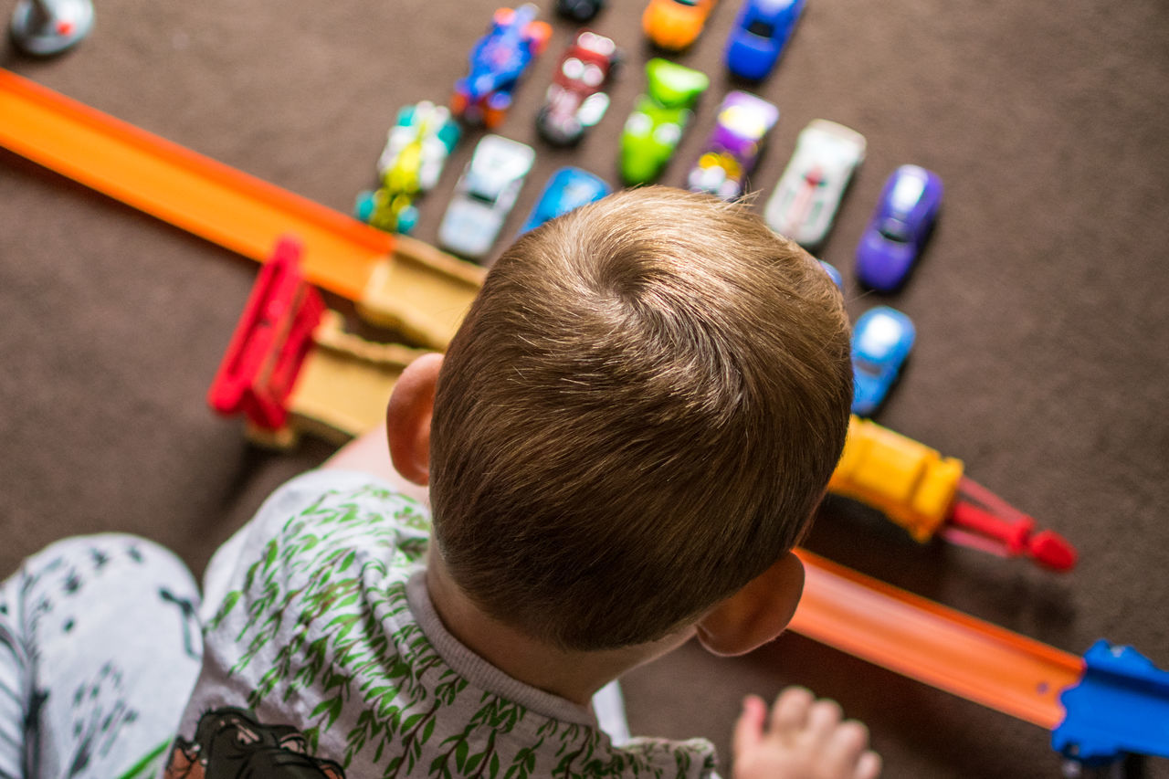 High Angle View Of Boy Playing With Toy Car At Home