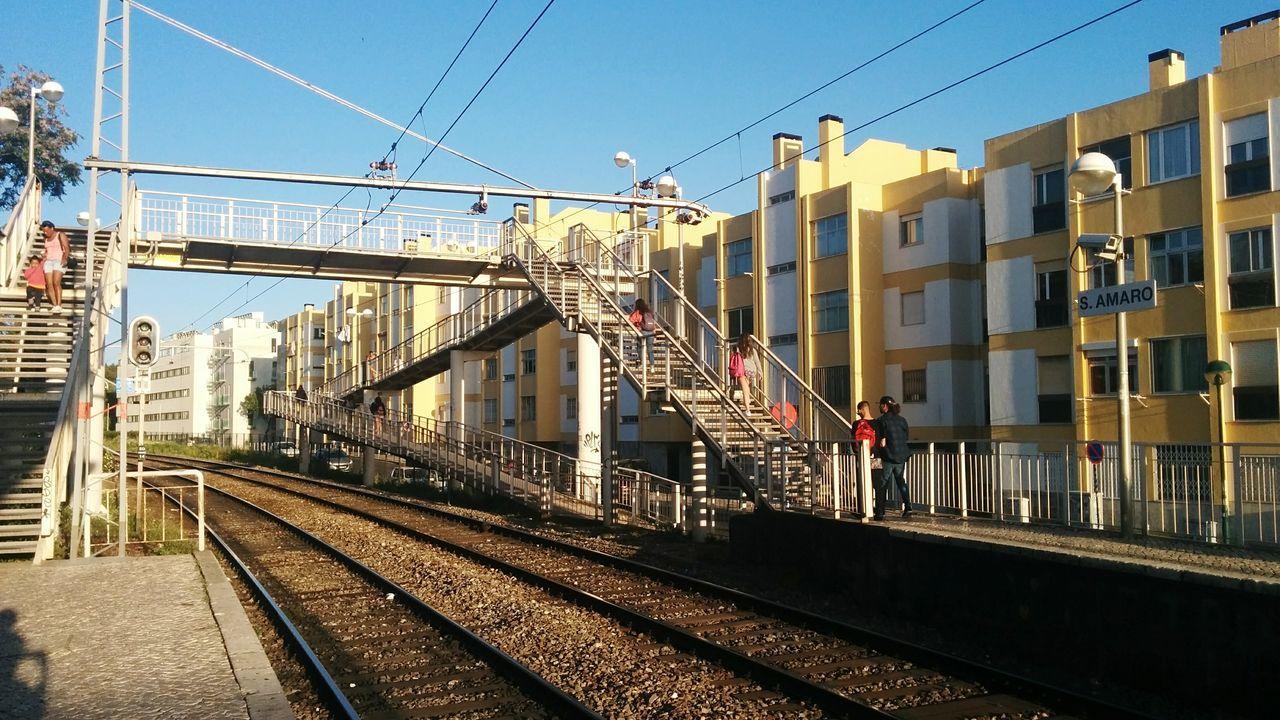 building exterior, built structure, architecture, transportation, railroad track, sky, clear sky, outdoors, sunlight, rail transportation, day, city, no people, public transportation