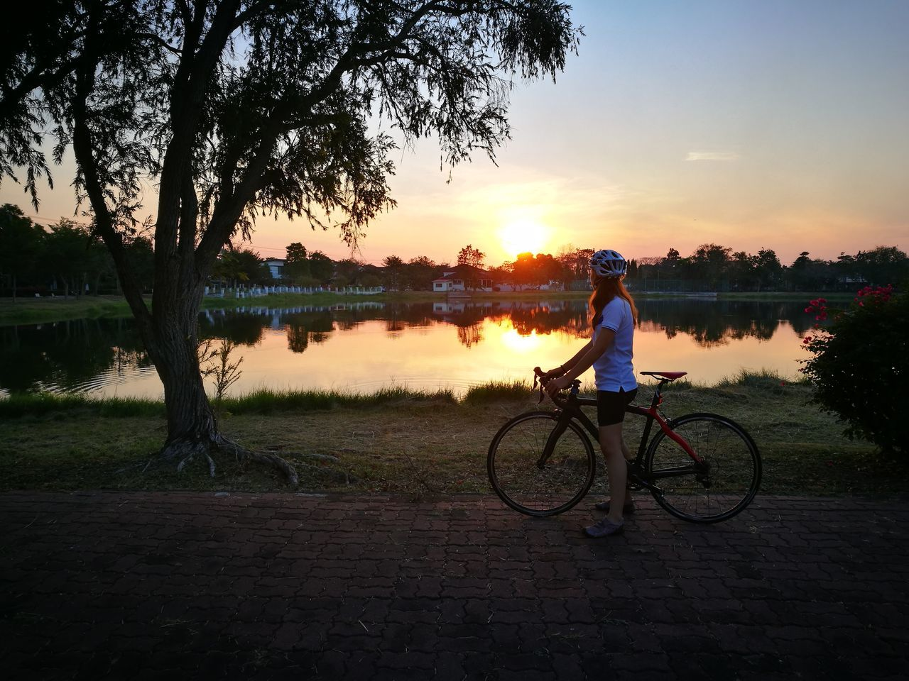 bicycle, sunset, tree, cycling, transportation, one person, full length, outdoors, sky, real people, nature, silhouette, water, mode of transport, lake, land vehicle, men, cycling helmet, bmx cycling, beauty in nature, grass, day, people