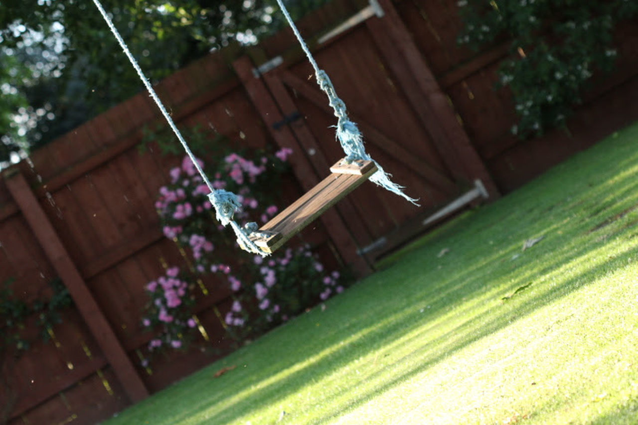Day Fence Flowers Grass Hanging Nature No People Outdoors Plant Playground Swing Swinging