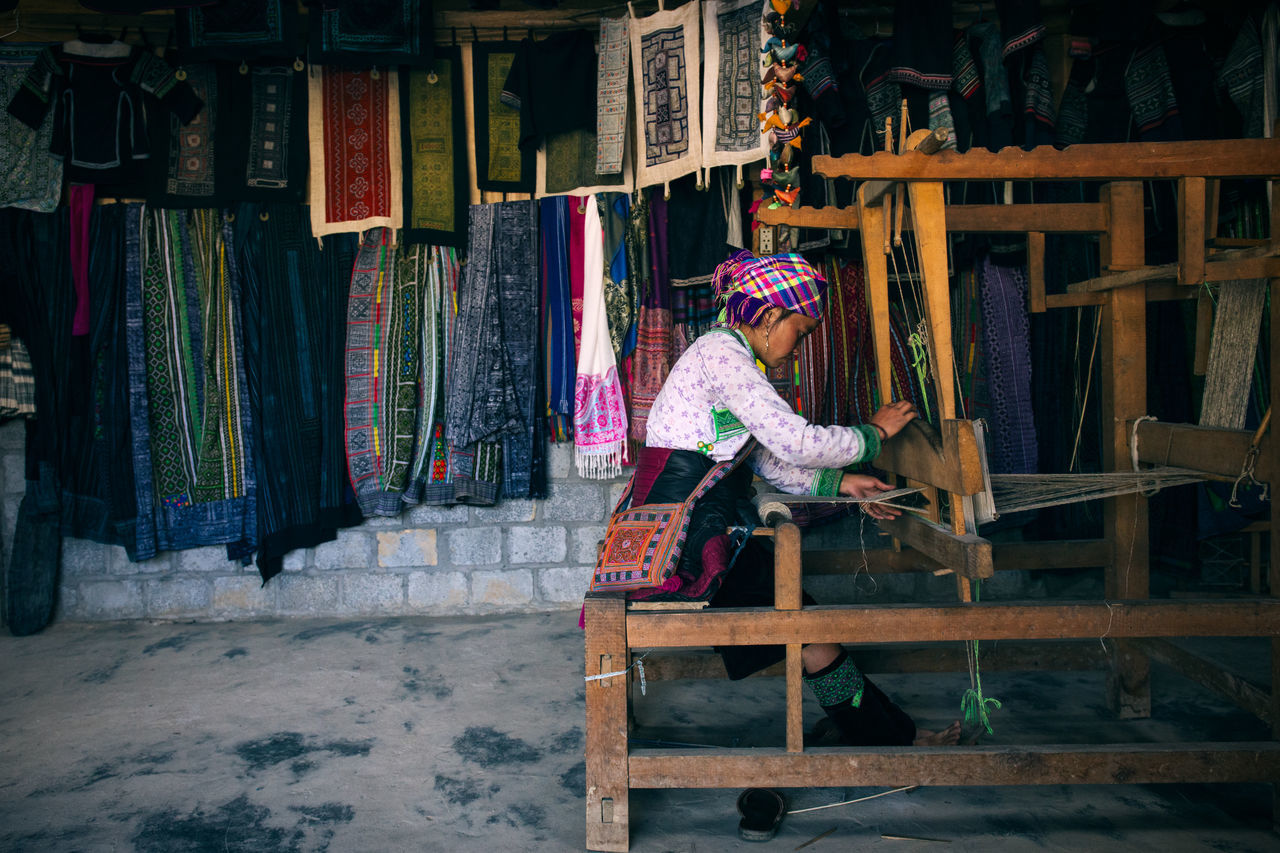 Traveling in Sapa, Vietnam women around the world cloth colorful creating Farm indigenous indoors Local making sew Sewing Sewing machine silk southeast asia store Travel travel destinations Travel Photography Traveling Tribal tribe Vietnam Vietnamese Weave