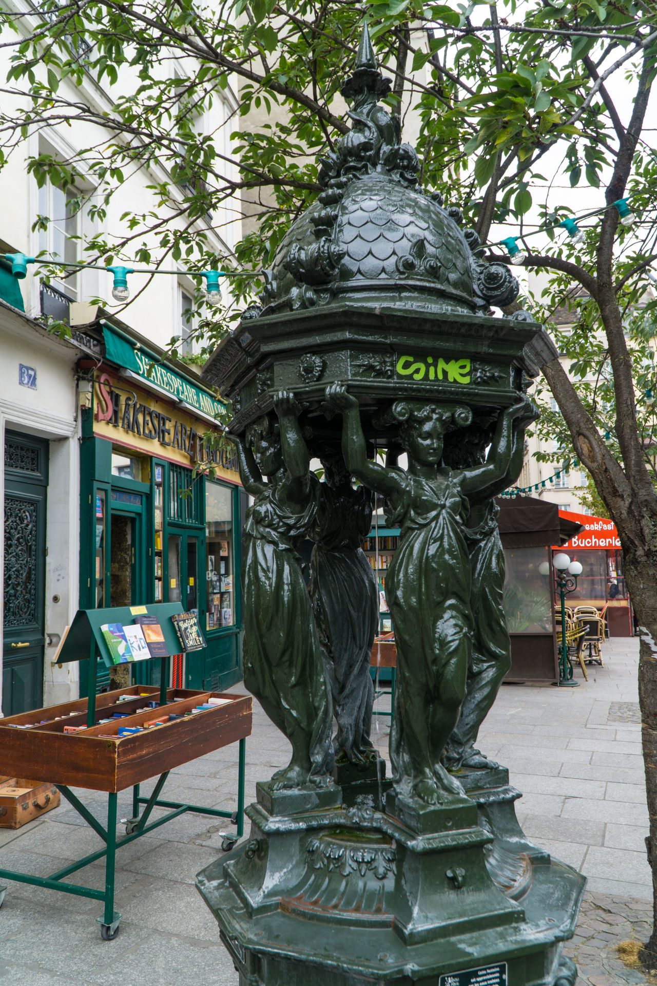 Water fountain in front of Shakespeare and Company book store, Paris, France Book Store Paris Sculptured Shakespeare And Company Paris Water Fountain