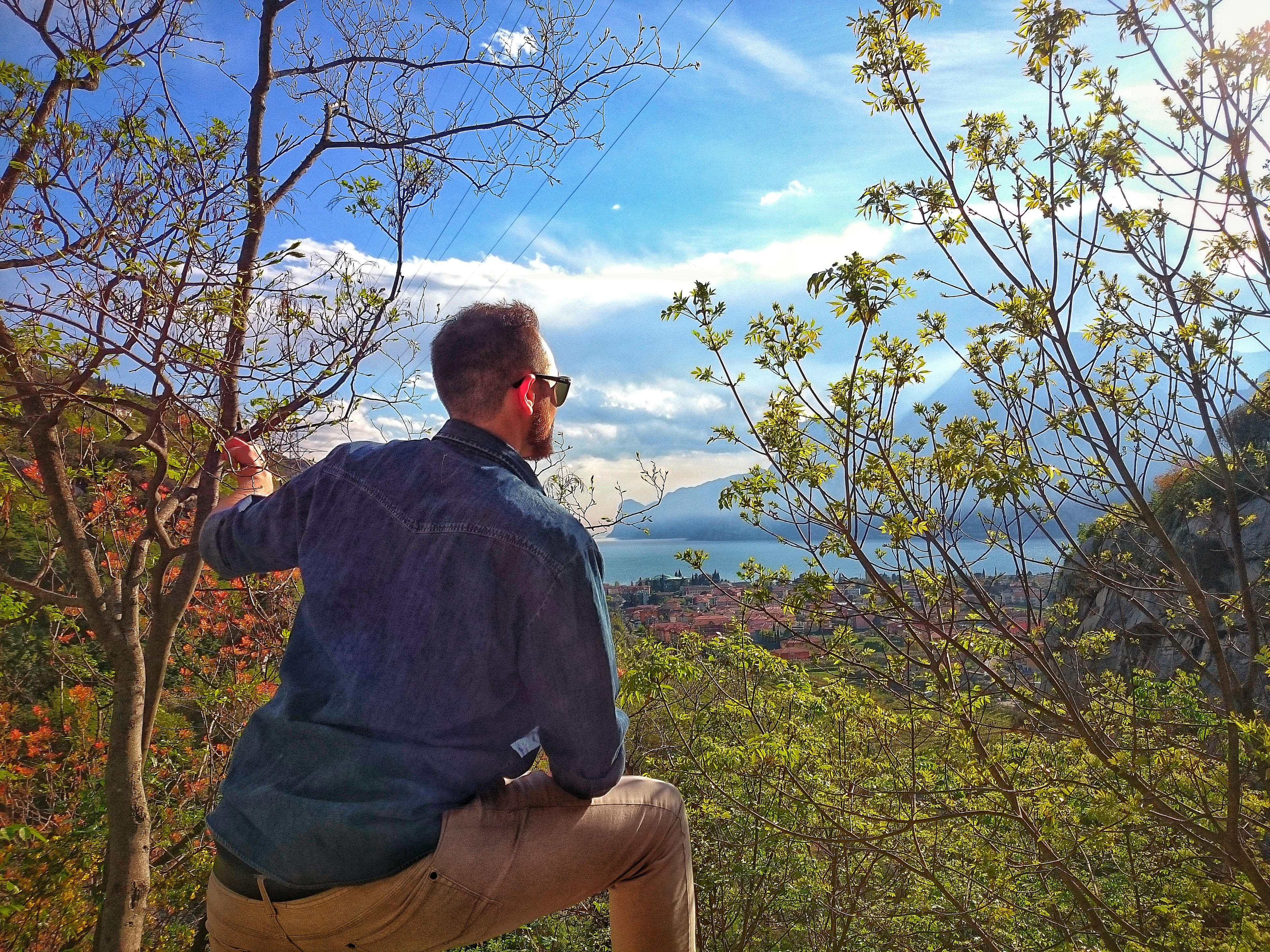sky, lifestyles, leisure activity, standing, waist up, cloud - sky, three quarter length, rear view, tree, casual clothing, nature, sitting, plant, relaxation, men, tranquility, person, beauty in nature