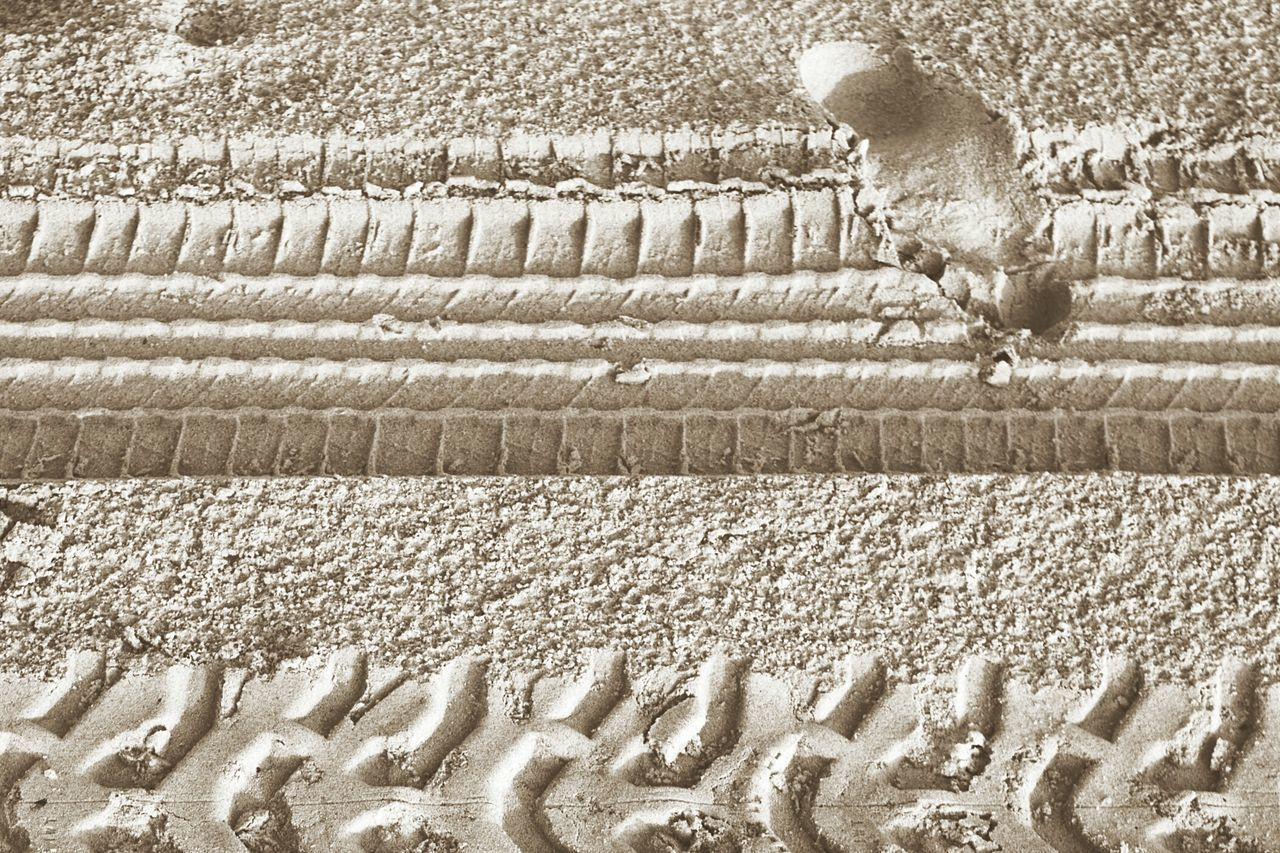 Close-Up Of Tire Tracks And Footprints On Sandy Beach
