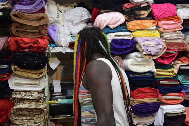 Abundance Adult Bazaar Business Business Finance And Industry Choice Clothing Clothing Store Colorful Colors Fabric For Sale Hat Horizontal Indoors  Large Group Of Objects Multi Colored People Person RASTA Retail  Sale Store Variation Young Men
