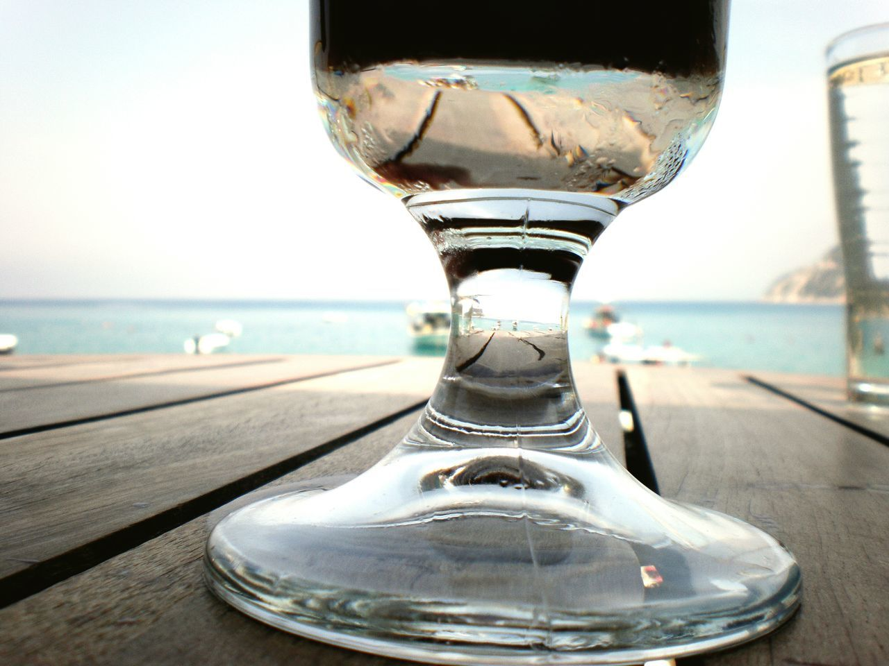 water, transparent, glass - material, sea, close-up, focus on foreground, indoors, table, drinking glass, glass, transportation, no people, day, drink, sky, horizon over water, clear sky, refreshment, empty, window