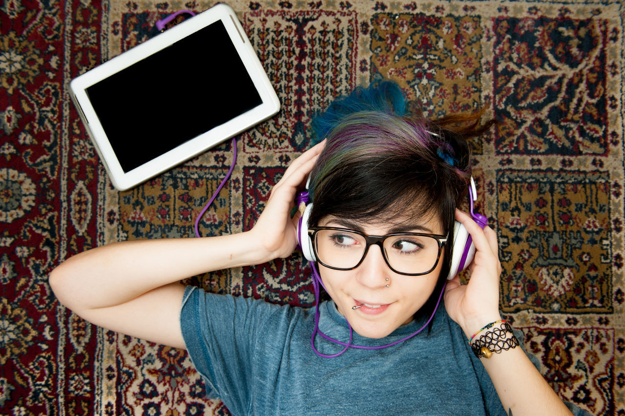 Young pretty teen woman happy listening music with tablet and headphones Alternative Blue Hair Cheerful Eyeglasses  Front View Girl Happy Headphone Headshot Hypster Indoors  Listening Music Lying Down One Person People Preety Real People Tablet Teen Teenager Woman Young