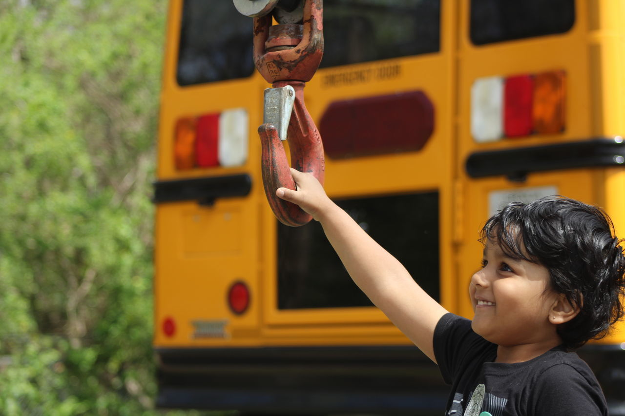 Playful Boy Smiling While Holding Metallic Hook By Bus