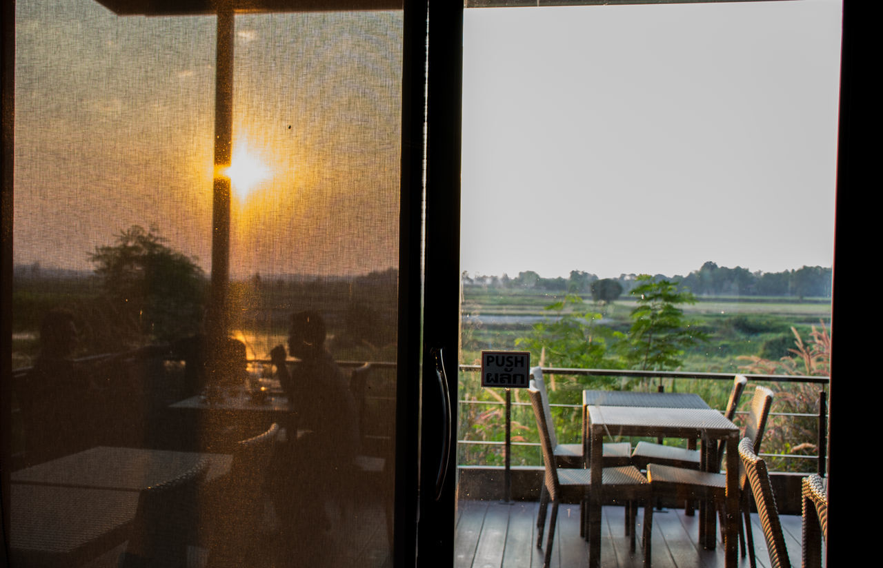 window, glass - material, table, indoors, chair, no people, tree, looking through window, clear sky, home interior, day, sunlight, nature, sky, sliding door, sunset