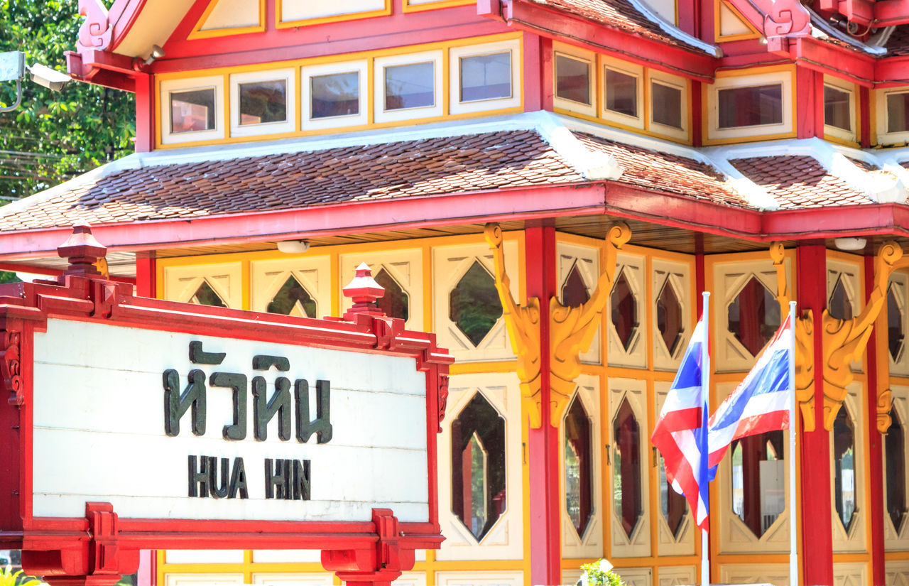 Hua Hin train station sign, with the building and Thai flag in the background Architecture Arrival Building Exterior Built Structure City City Life Commuter Country Countryside Day Journey Non-western Script Outdoors Railway Station Railway Station Platform Sign Station Thai Culture Thai Flag Thailand Train Station Travel