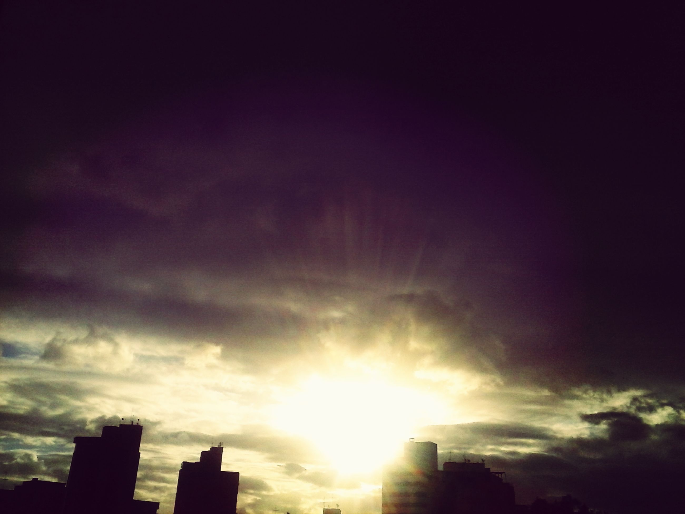 low angle view, sky, sun, silhouette, built structure, building exterior, architecture, cloud - sky, sunbeam, sunset, sunlight, cloud, cloudy, nature, beauty in nature, city, lens flare, outdoors, no people, scenics