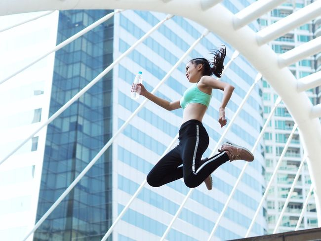 Sport woman joyful and jumping over modern building background. Jump Architecture Balance Building Exterior Built Structure Concentration Day Exercising Flexibility Full Length Healthy Lifestyle Leisure Activity Lifestyles Low Angle View Mid-air One Person Outdoors Practicing Real People Skill  Sport Woman Sports Clothing Young Adult Young Women