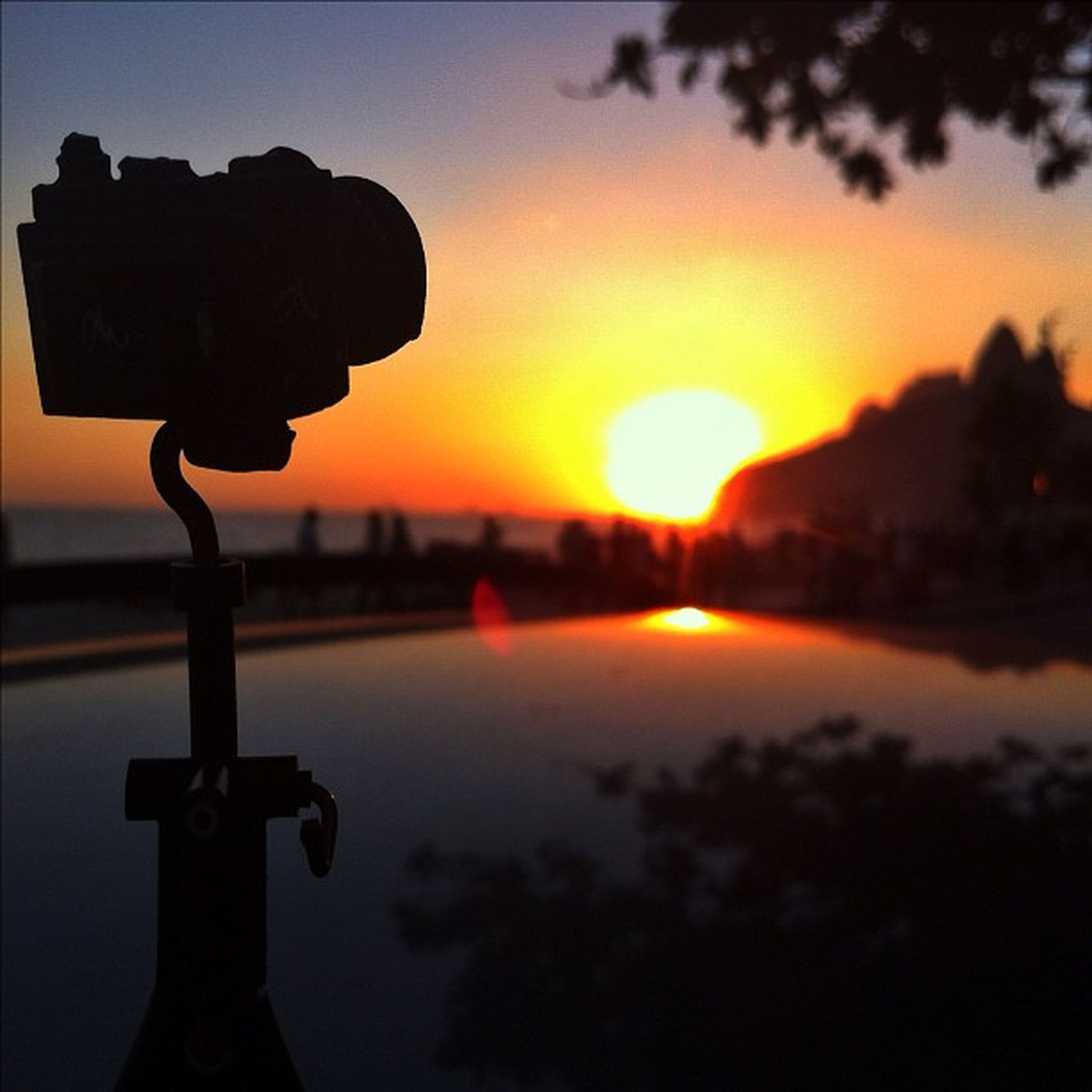 sunset, silhouette, orange color, sky, sun, scenics, tranquility, beauty in nature, tranquil scene, nature, focus on foreground, idyllic, sunlight, water, outdoors, close-up, reflection, dusk, no people, cloud - sky