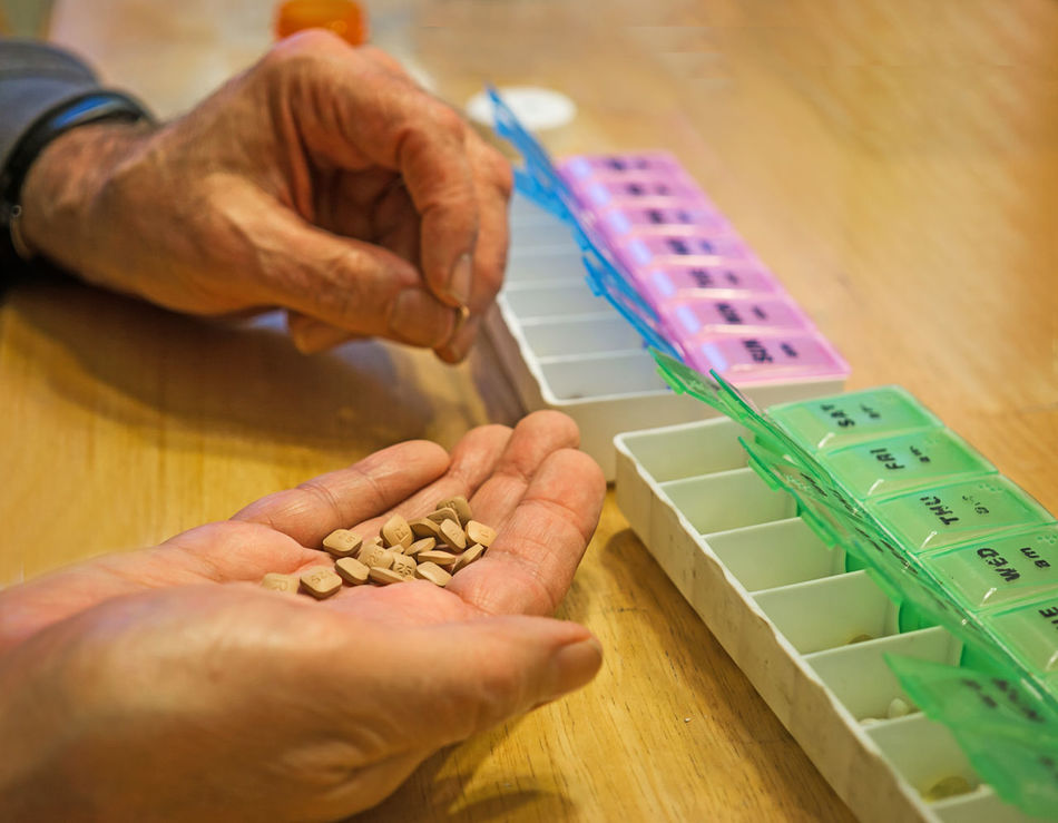 Sorting pills--a weekly chore Close-up Day Elderly Fingers Health Holding Human Body Part Human Hand Indoors  Medicines Men One Person People Pill-boxes Real People Skill  Sorting  Table Vitamins Working