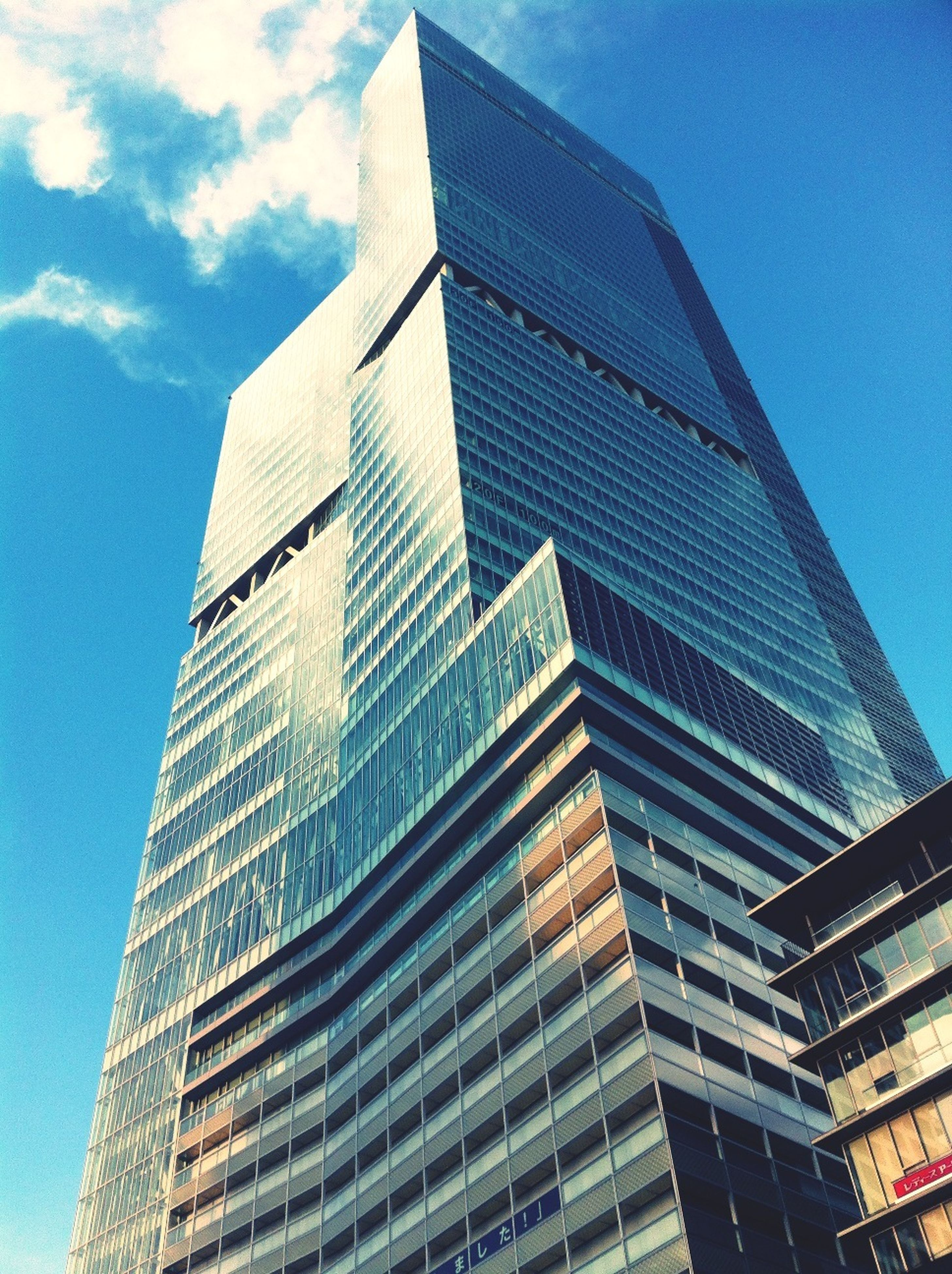 building exterior, architecture, low angle view, built structure, modern, skyscraper, office building, tall - high, city, tower, sky, glass - material, building, tall, reflection, day, outdoors, city life, no people, blue