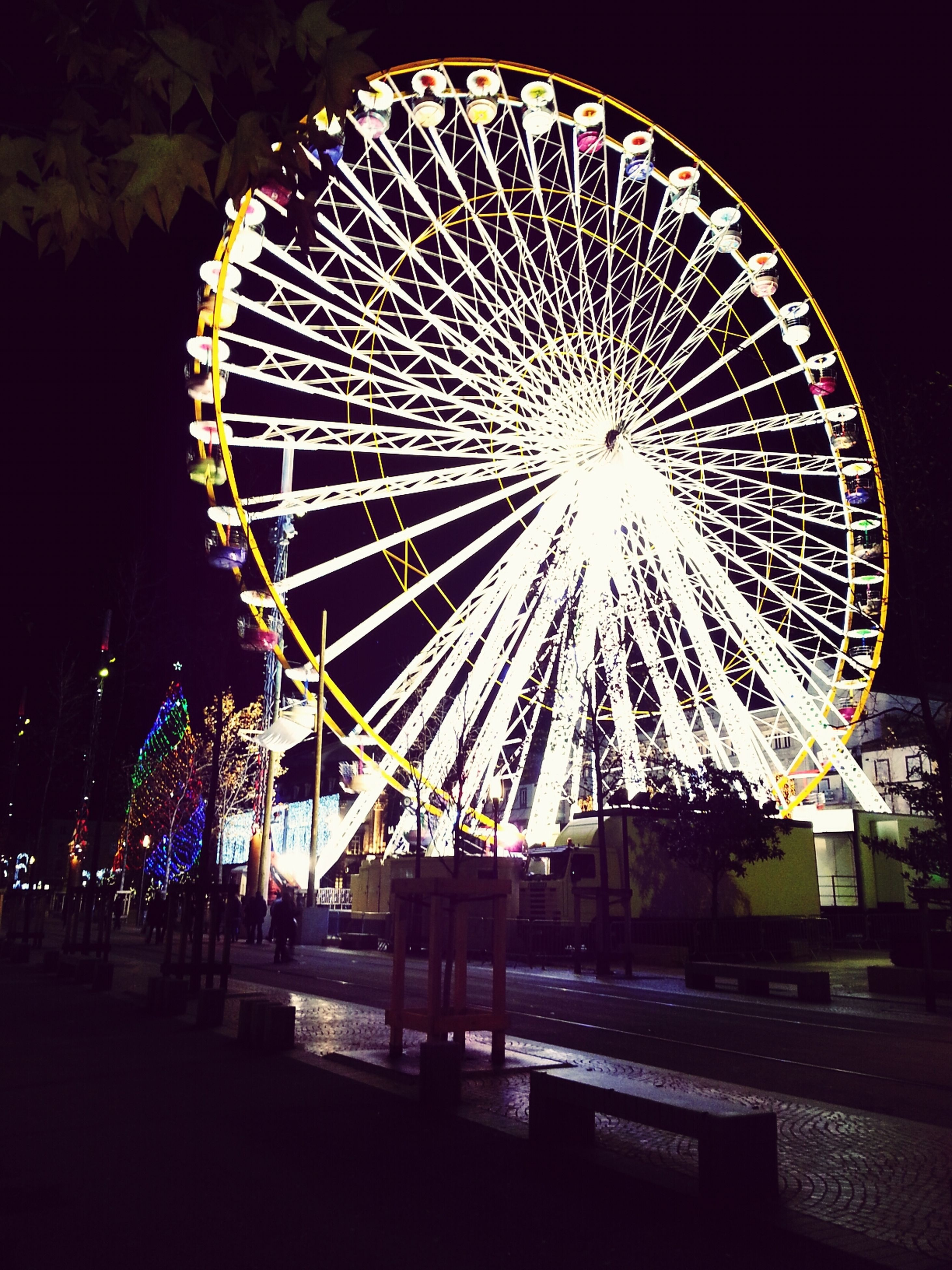 night, illuminated, arts culture and entertainment, ferris wheel, built structure, amusement park, amusement park ride, low angle view, architecture, sky, glowing, outdoors, long exposure, building exterior, no people, circle, incidental people, street light, city, lighting equipment