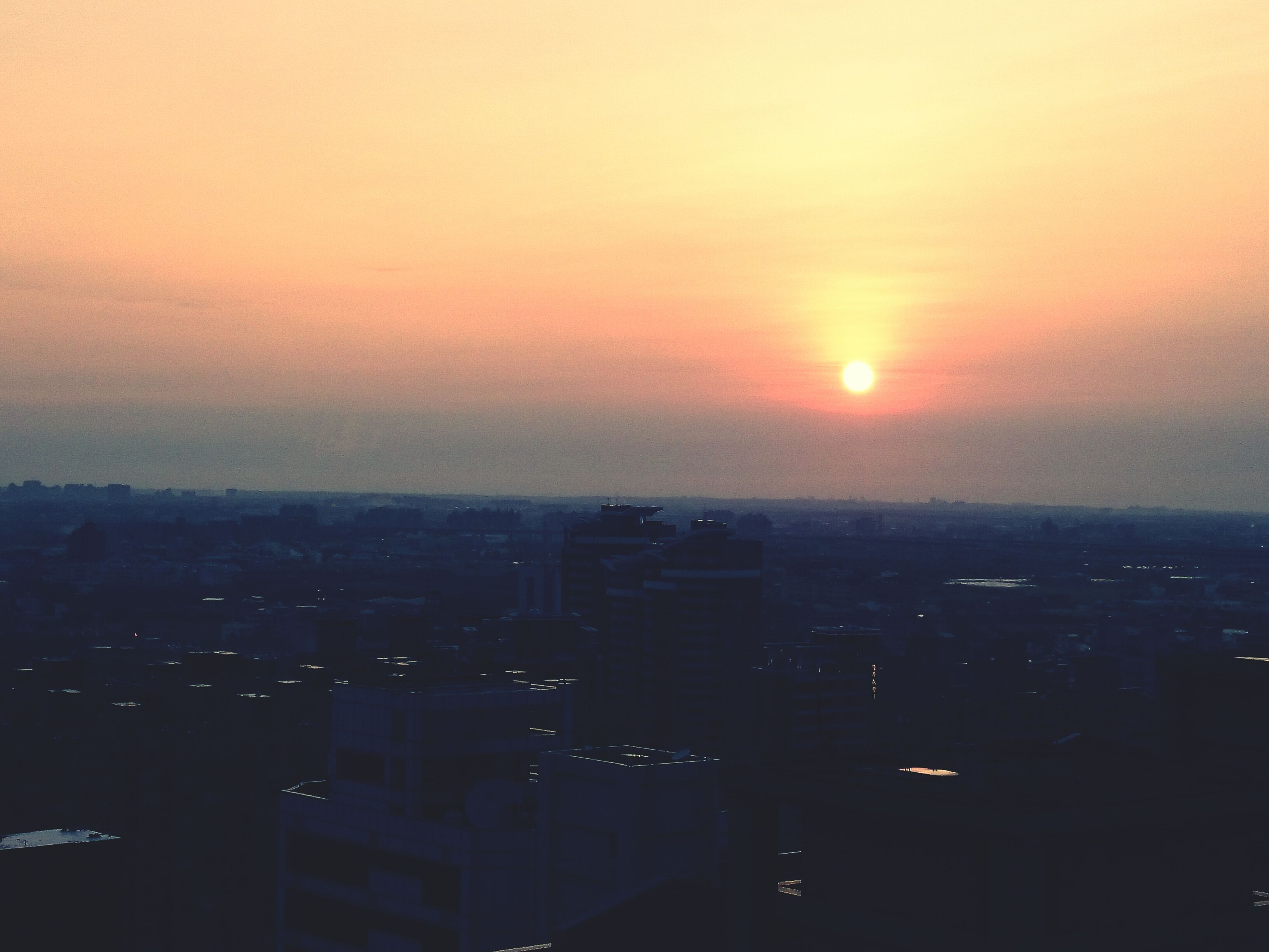 sunset, cityscape, orange color, building exterior, city, architecture, built structure, sun, crowded, sky, scenics, silhouette, high angle view, copy space, residential district, residential building, residential structure, beauty in nature, outdoors, no people