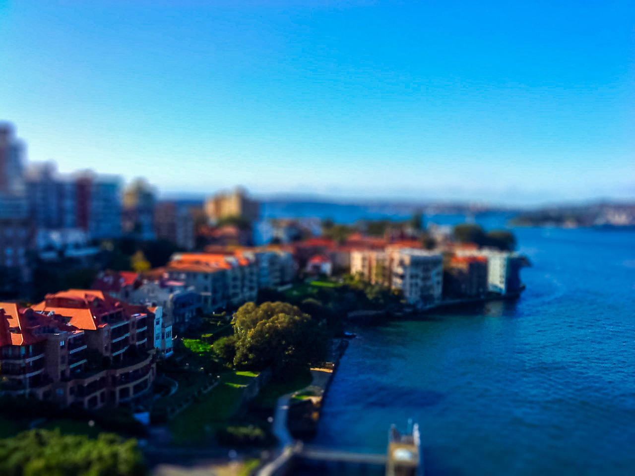 Tilt Shift Image Of City By Sea Against Clear Blue Sky