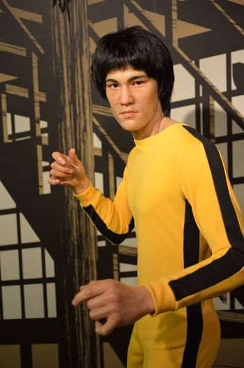Bruce Lee Casual Clothing Composition Confidence  Contemplation Fashion Front View Happiness Indoors  Leisure Activity Lifestyles Madame Tussauds Men Perspective Portrait Real People Serious Standing Three Quarter Length Waist Up Wall Wax Dolls Wax Museum Young Adult Young Men
