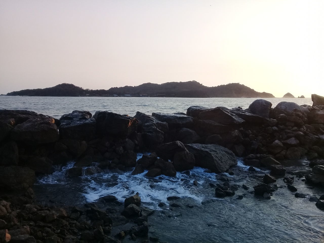 sea, nature, rock - object, water, beauty in nature, clear sky, scenics, tranquil scene, beach, tranquility, outdoors, pebble, no people, sky, pebble beach, horizon over water, day