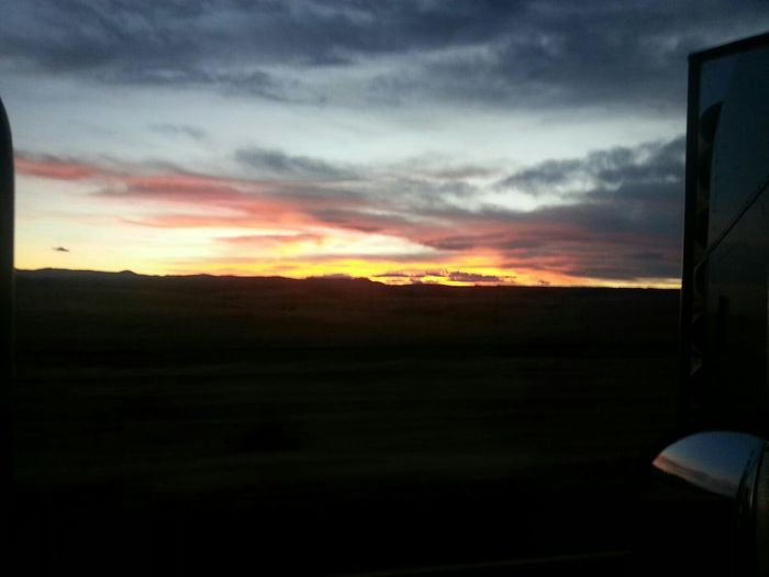 Sunsets Seen Over The Road Beautiful Sunset Yellow, Orange, Pink, Red, Blue Clouds Clouds And Sky Mountains Over The Road Mirror Of The Semi