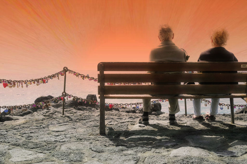 Mature couple surrounded by friendship locks sitting side by side on wooden bench and looks on the sea Adult Alienation Beach Bench Chair Connectedness Day Elderly Man Elderly Woman Eventide Friendship Locks Loneliness And Sadness Lonely Love Love In The Age Marital Bliss Outdoors People Rear View Separation Symbol Symbolic  Togetherness Watching The Sunset