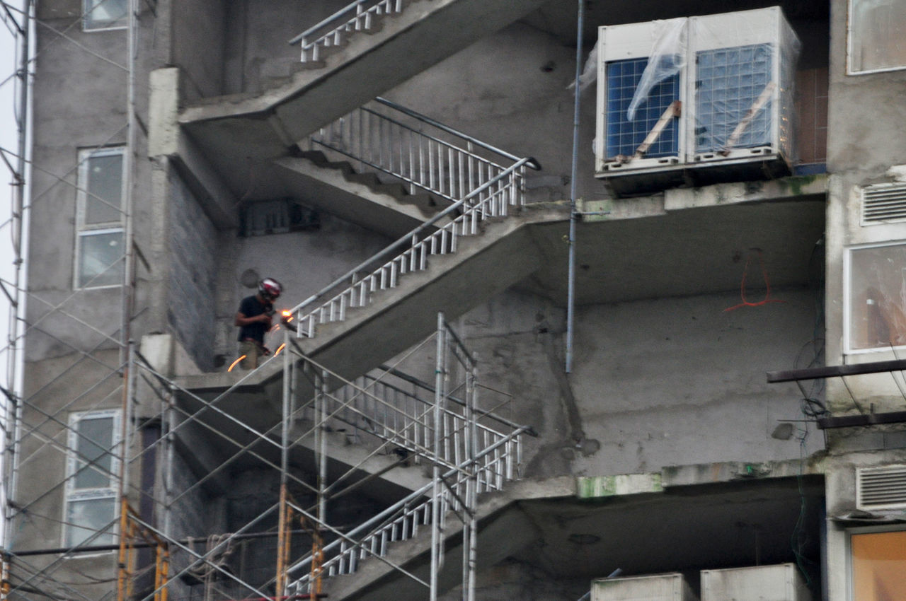 Worker welding handrails for staircase in apartment building under construction in Da Nang, Vietnam. Apartments Architecture Building Exterior City Construction Da Nang Full Length Iron Railings Lifestyles Men Occupation Outdoors Staircase Vietnam Welders Welding Workers Working