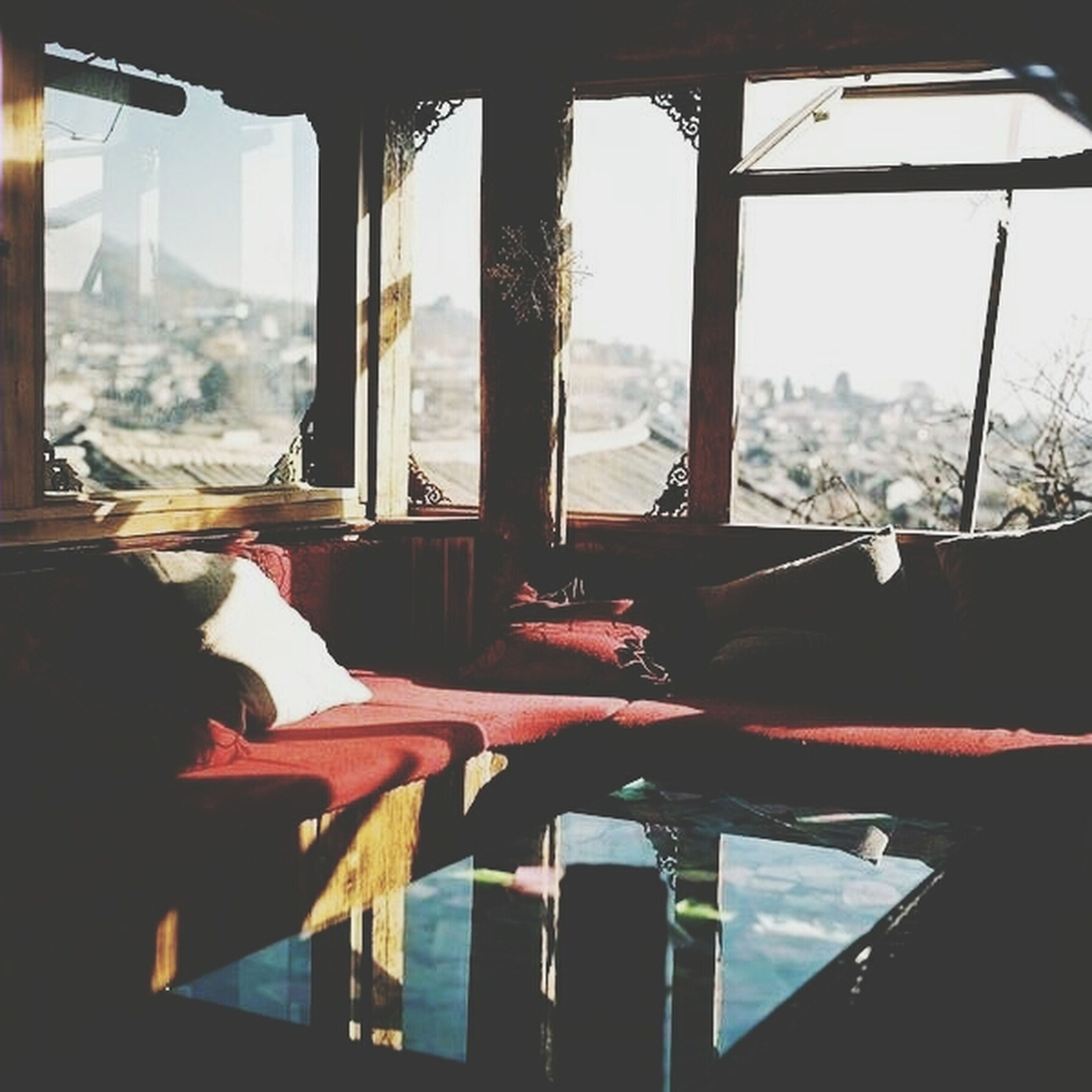 indoors, window, glass - material, transparent, table, restaurant, chair, sitting, glass, looking through window, home interior, vehicle interior, reflection, lifestyles, drinking glass, relaxation, day, sunlight