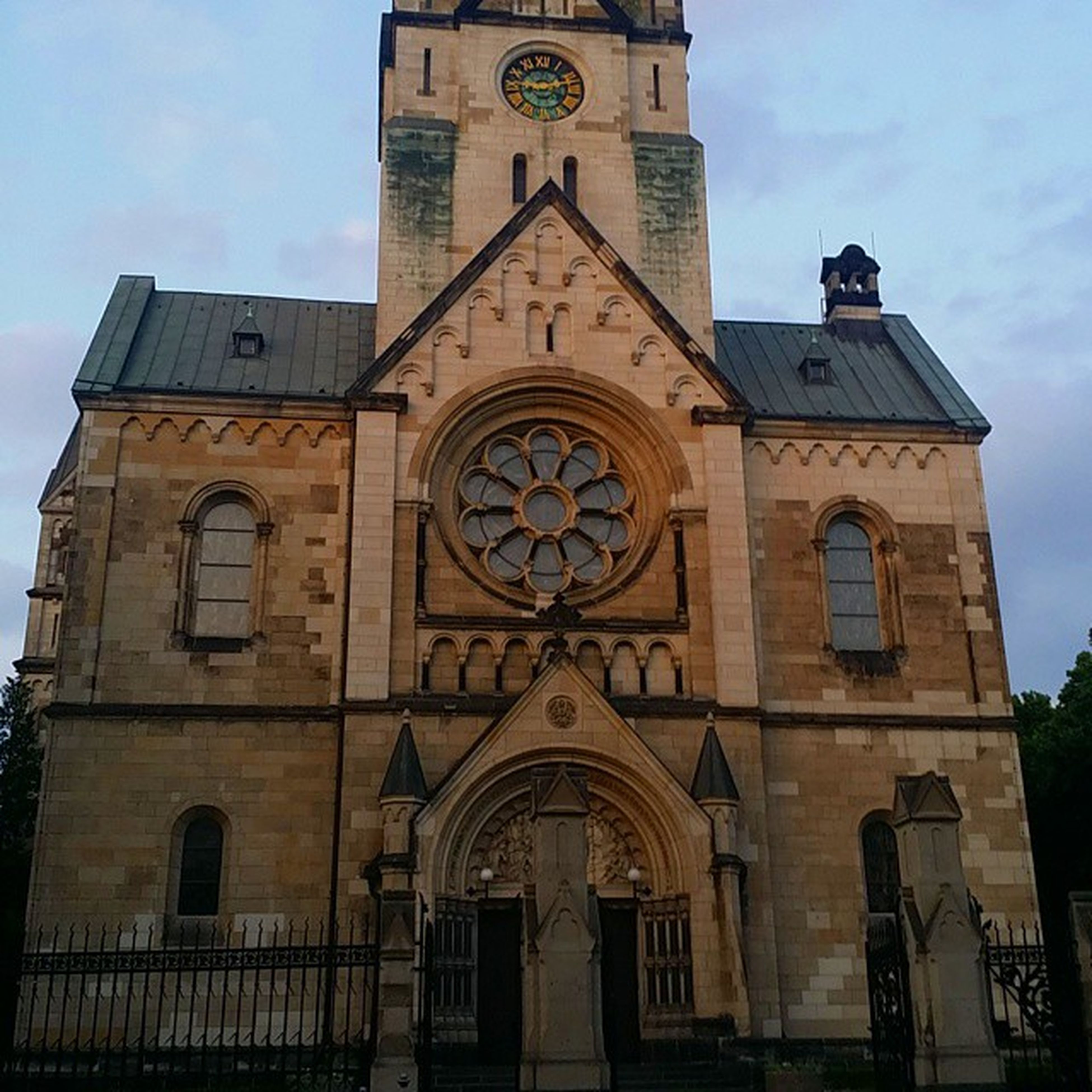 architecture, low angle view, building exterior, built structure, religion, clock, sky, church, clock tower, time, cross, place of worship, window, facade, spirituality, tower, day, no people