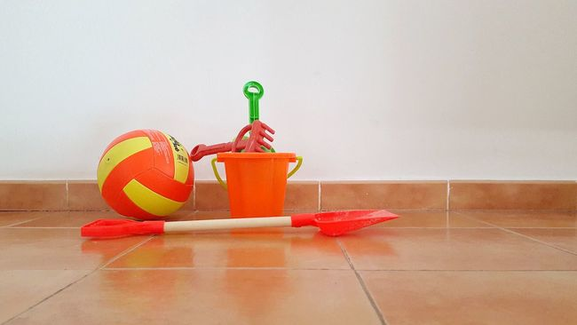 Ball Beach Equipments Bucket Centerpiece Childhood Children Playing Domestic Life Flooring For Children For The Beach Freshness Game Holiday Indoors  Let´s Go To The Beach Orange Color Playing Red Refreshment Shovel Still Life Surface Level Table Tiled Floor