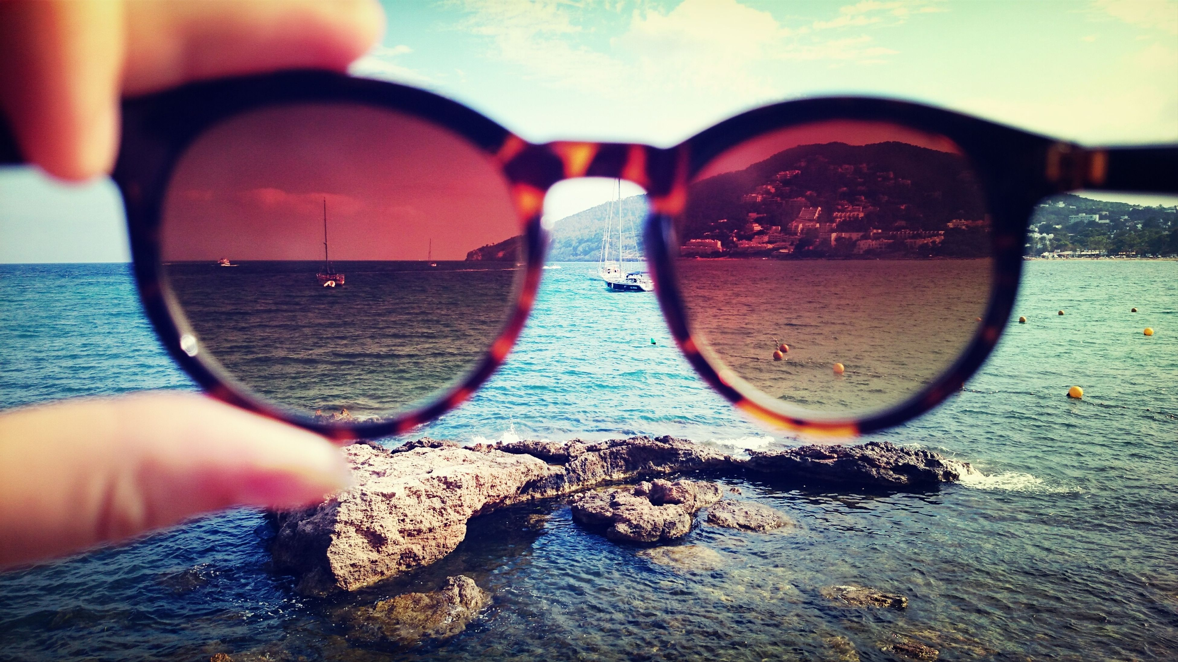 water, leisure activity, lifestyles, part of, sunglasses, reflection, person, sea, cropped, holding, vacations, transportation, close-up, unrecognizable person, sky, beach, mode of transport