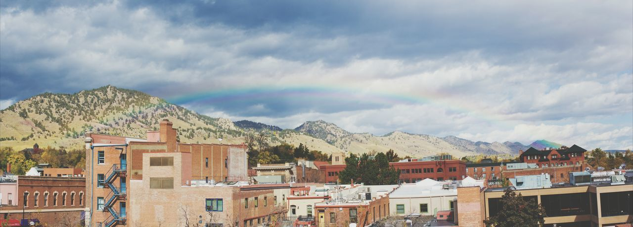 Rainbow over the city. Panorama Landscape