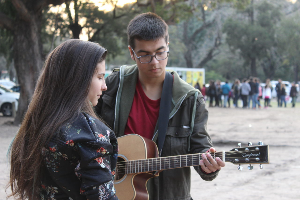 two people, guitar, music, leisure activity, togetherness, focus on foreground, lifestyles, playing, real people, day, casual clothing, outdoors, standing, musical instrument, young adult, plucking an instrument, tree, people