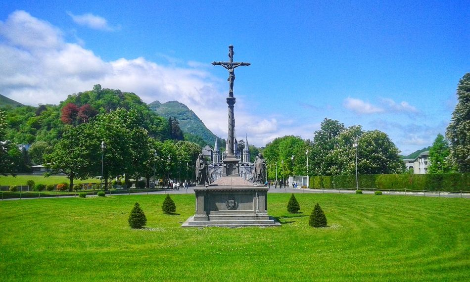 Lourdes sanctuary by Jim Delmont Sky Grass Outdoors No People Tree Tranquility Cross Catholic Cross Lourdes Serenity Beautiful Sky Green Grass 🌱 Uhdphotography Clouds And Sky