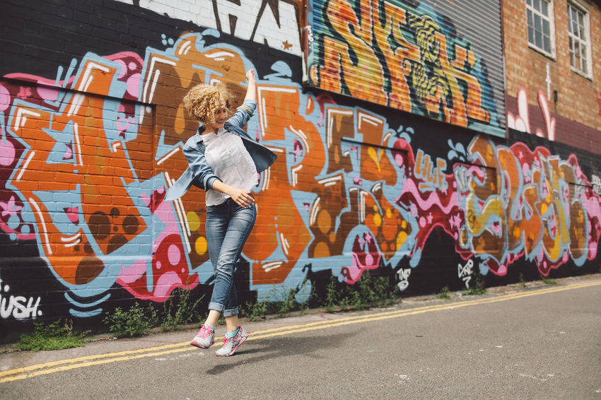 Art Blonde Brighton Casual Clothing City City Life Curly Hair Day Full Length Girl Graffiti Graffiti Graffiti Art Joyful Jumping Leisure Activity Lifestyles Multi Colored Outdoors Playful Spinning Street Art People And Places Art Is Everywhere Live For The Story Connected By Travel Fashion Stories