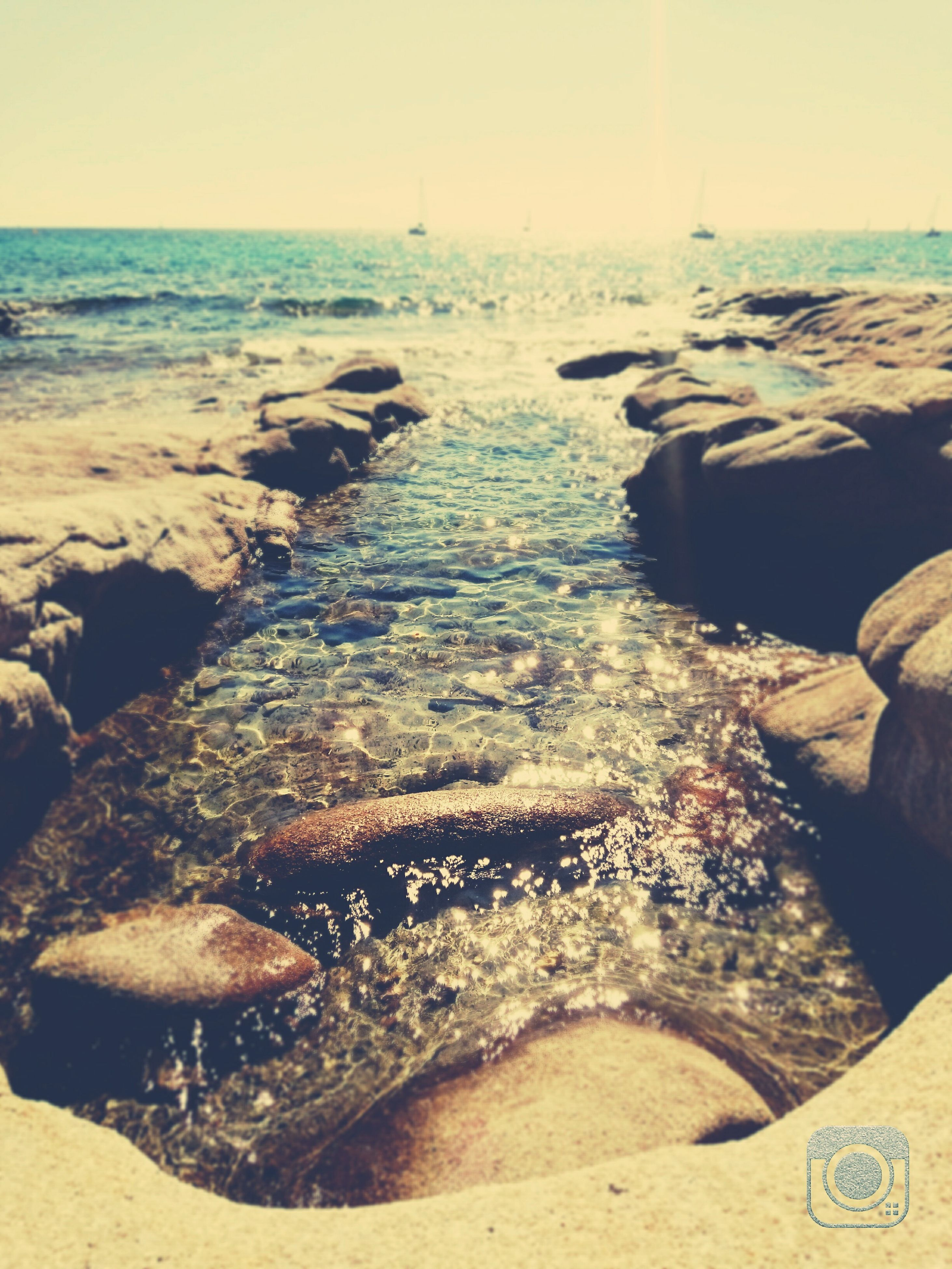 beach, sea, sand, water, shore, tranquil scene, tranquility, rock - object, scenics, nature, clear sky, sunlight, beauty in nature, horizon over water, high angle view, coastline, outdoors, day, idyllic, rock formation