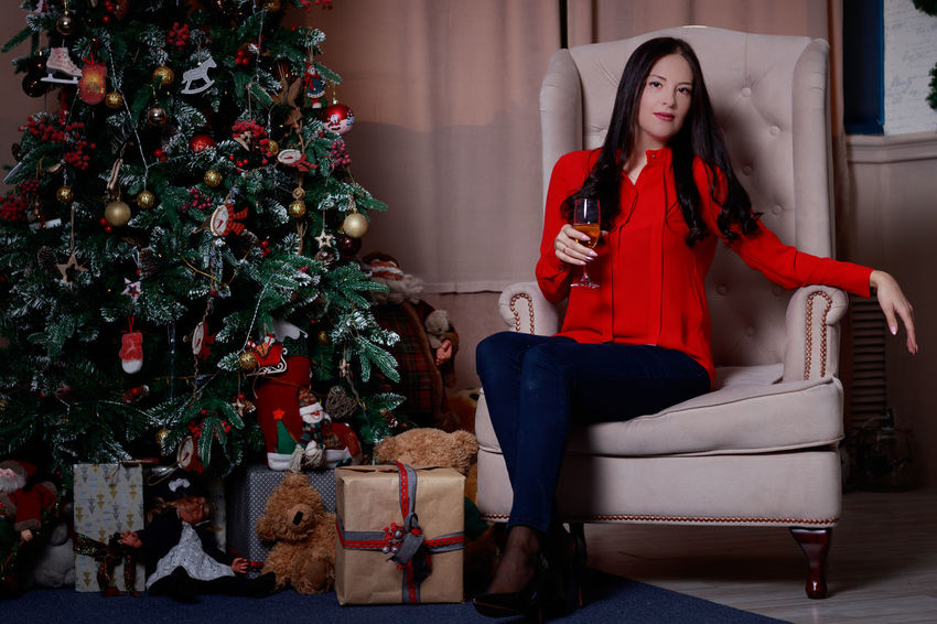 EyeEmSelect Beautiful Woman Celebration Christmas Christmas Decoration Christmas Present Christmas Tree Domestic Life Full Length Home Interior Living Room One Person One Woman Only Real People Red Sitting Sofa Young Adult Young Women