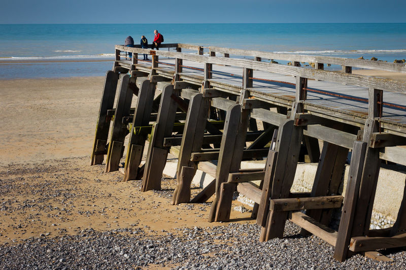 Tourists enjoying sea view from pier during low-tide, Normandy, France. Beach Day Horizon Over Water Jetty Looking Out To Sea Low Tide Nature Normandy Normandy Beach Outdoors Pebbles Pier Real People Red Jacket Sand Sea Shore Stone Tourists Water Wood